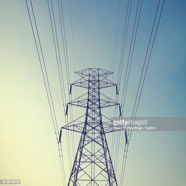 low angle view of electricity pylon against clear sky - power line stock photos and pictures