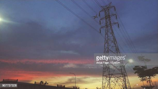 low angle view of electricity pylon against cloudy sky during sunset - electrical component stock photos and pictures