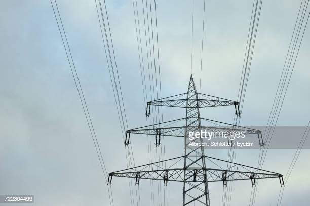 low angle view of electricity pylon against cloudy sky - albrecht schlotter stock-fotos und bilder