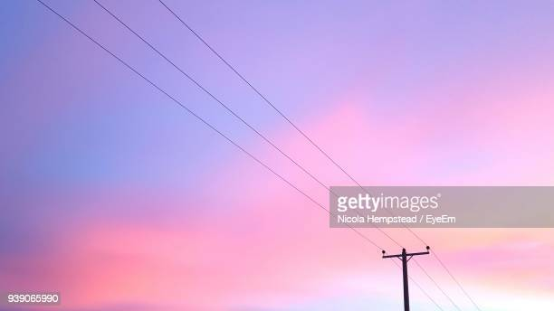 low angle view of electricity pylon against sky at sunset - power line stock pictures, royalty-free photos & images