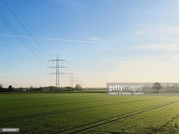 Low Angle View Of Electricity Pylon On Agricultural Field Against Sky