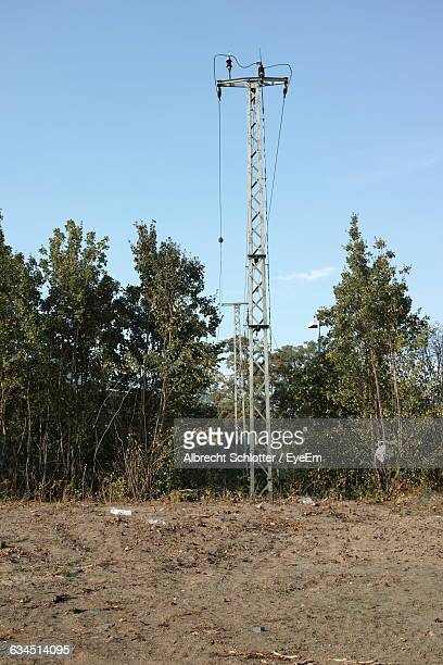 low angle view of electricity pylon on field against sky - albrecht schlotter stock photos and pictures
