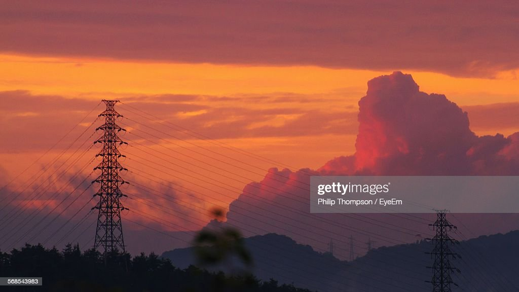 Low Angle View Of Electricity Pylons Against Cloudy Sky During Sunset : Stock Photo