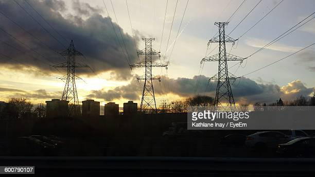 Low Angle View Of Electricity Pylons Against Sky During Sunset
