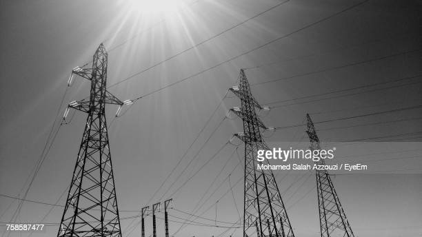 low angle view of electricity pylons against sky - salah stock photos and pictures