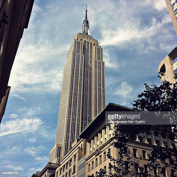 low angle view of empire state building against sky - empire state building stock pictures, royalty-free photos & images
