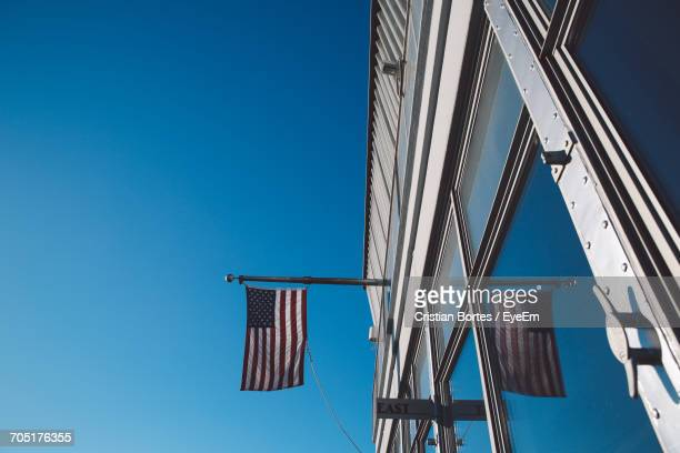 Low Angle View Of Empire State Building With American Flags Against Clear Sky