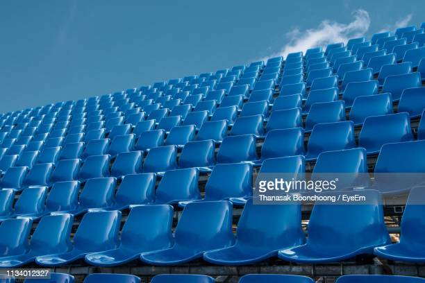low angle view of empty blue chairs against sky - abwesenheit stock-fotos und bilder