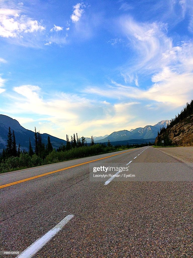 Low Angle View Of Empty Road By Trees Against Cloudy Sky : Stock Photo