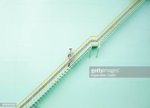 low angle view of engineer walking on steps - steps stock photos and pictures