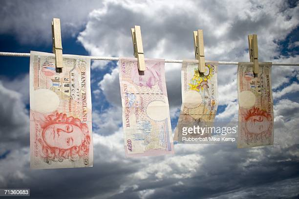 low angle view of english paper currency pegged on a clothesline - money laundering stock photos and pictures