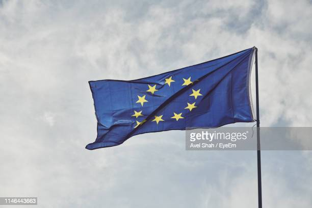 low angle view of european union flag against blue sky - british and eu flag stock pictures, royalty-free photos & images