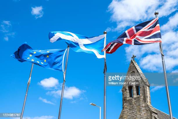 low angle view of european union, scotland and great britain flags flying against blue sky. - scotland stock pictures, royalty-free photos & images