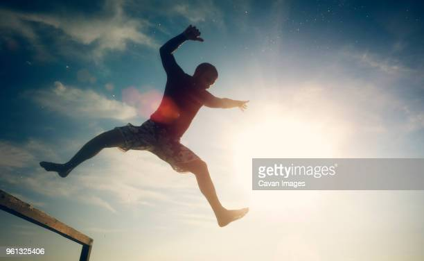 Low angle view of excited man in mid-air against sky on sunny day