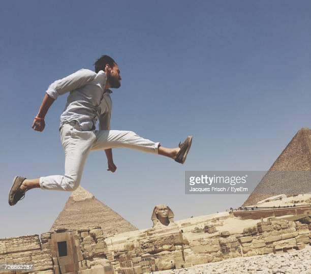 Low Angle View Of Excited Man Jumping Against Clear Sky