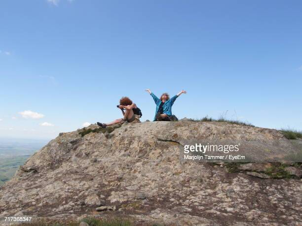 Low Angle View Of Excited Women Sitting On Rock Against Sky