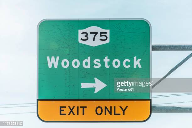 low angle view of exit road sign at highway against sky - exit sign stock pictures, royalty-free photos & images