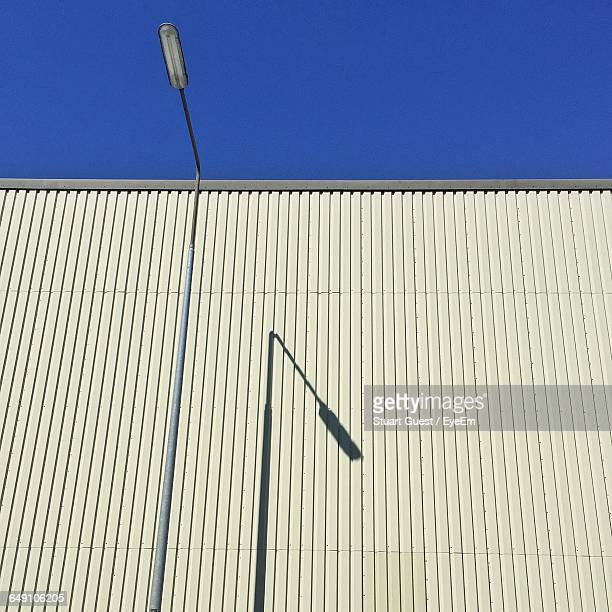 Low Angle View Of Factory Against Clear Blue Sky During Sunny Day