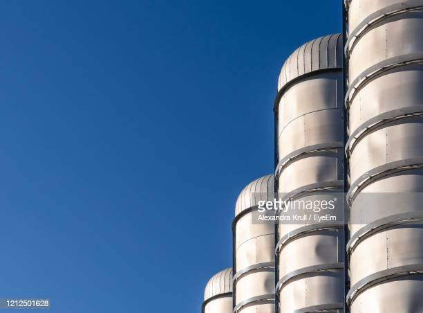 low angle view of factory against clear blue sky - alexandra krull stock-fotos und bilder