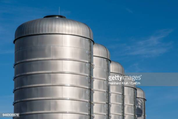 low angle view of factory against sky - fuel storage tank stock photos and pictures