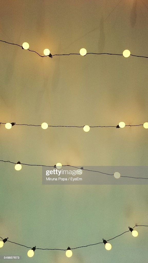 Low Angle View Of Fairy Lights Against White Wall