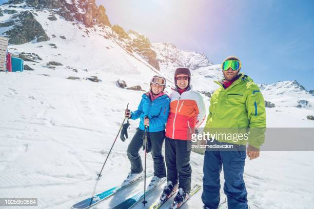 low angle view of family on ski slopes in switzerland, ski holidays 3 people enjoying swiss alps and vacations concept - ski holiday stock photos and pictures