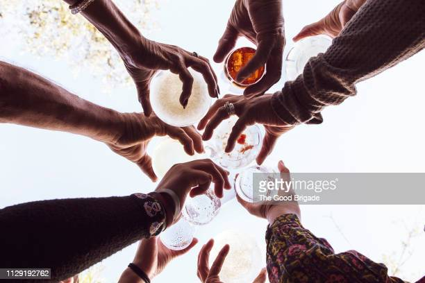 low angle view of family toasting with drinks at party - honour stock pictures, royalty-free photos & images