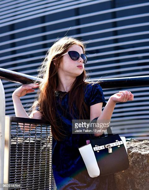 Low Angle View Of Fashionable Girl Standing With Purse Against Building