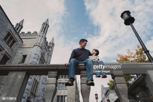 low angle view of father and son sitting on railing against cloudy sky in city - kingston ontario stock photos and pictures