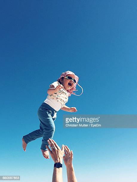 Low Angle View Of Father Catching Daughter Against Blue Sky