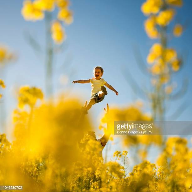 low angle view of father holding son amidst yellow flowering plant against sky - cuadrado composición fotografías e imágenes de stock