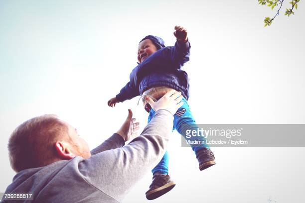 Low Angle View Of Father Playing With Baby Against Clear Sky