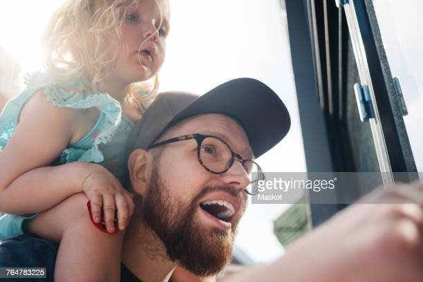 Low angle view of father talking while carrying daughter on shoulders during sunny day