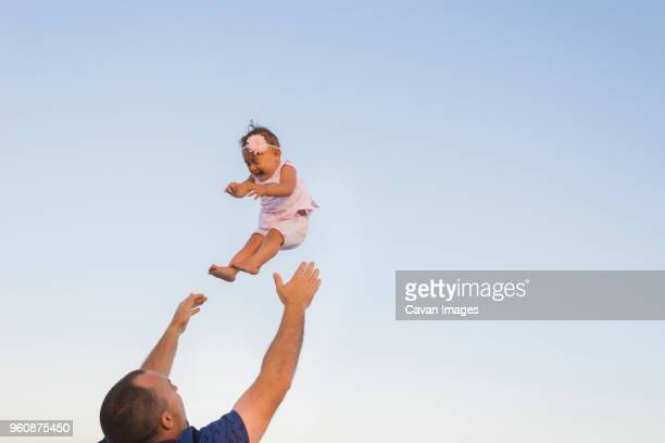 Low angle view of father throwing daughter into air against clear sky