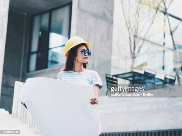 Low Angle View Of Female Architect Holding Blueprint While Standing Against Building