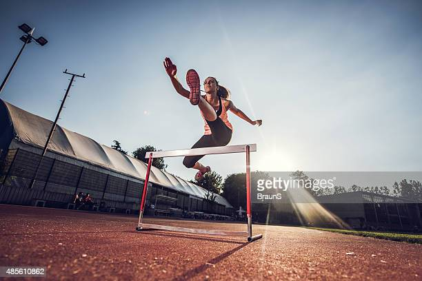 low angle view of female athlete hurdling on sports race. - sportsperson stock pictures, royalty-free photos & images