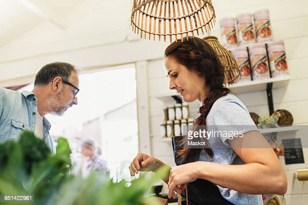 Low angle view of female clerk with mature customer at food store