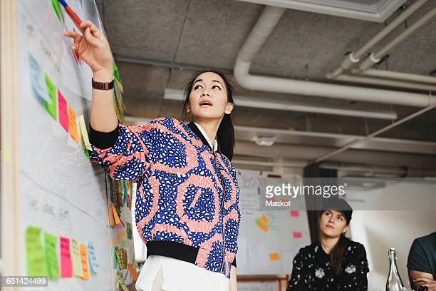 Low angle view of female engineer explaining coworkers during meeting