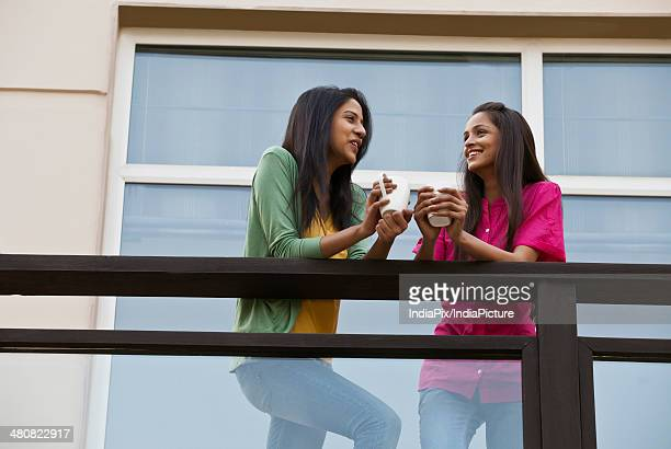 Low angle view of female friends conversing while having coffee in balcony