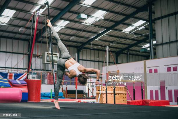 low angle view of female gymnast practicing aerial cartwheel - legs apart stock pictures, royalty-free photos & images