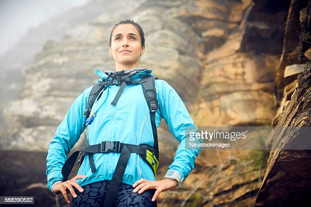 low angle view of female hiker standing against rock formation - arms akimbo stock photos and pictures