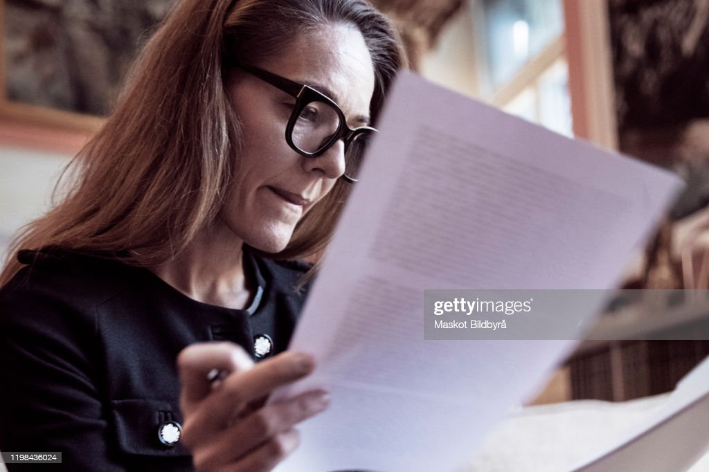 Low angle view of female professional analyzing documents at law firm : Stock Photo