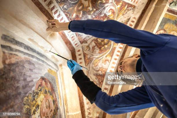 low angle view of female restorer working on paintings in antique catholic church - stock photo - restoration style stock pictures, royalty-free photos & images