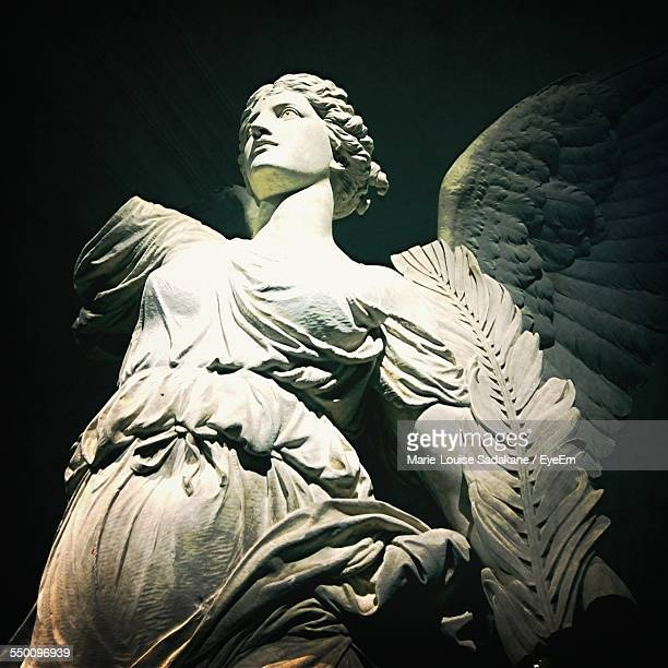 Low Angle View Of Female Statue Against Sky At Night