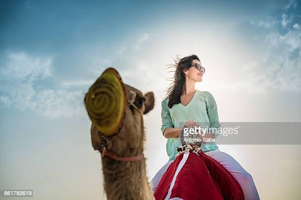 Low angle view of female tourist riding camel in desert, Dubai, United Arab Emirates