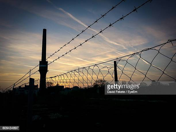 Low Angle View Of Fence Against Sky At Sunset
