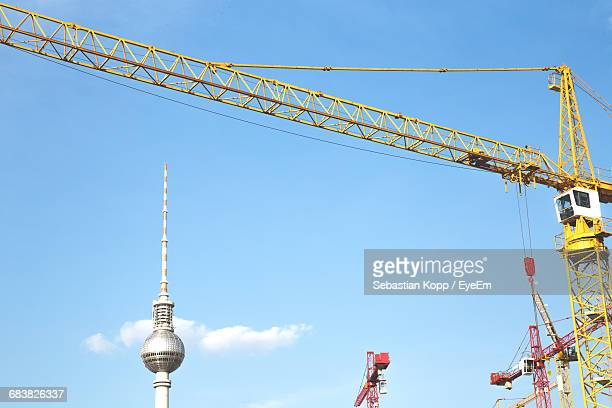 Low Angle View Of Fernsehturm And Cranes Against Sky
