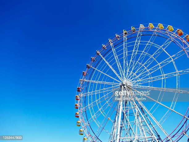low angle view of ferris wheel against blue sky - 観覧車 ストックフォトと画像