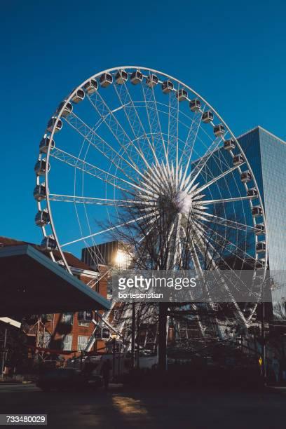 low angle view of ferris wheel against blue sky - bortes fotografías e imágenes de stock