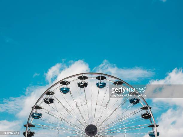 low angle view of ferris wheel against blue sky - ferris wheel stock pictures, royalty-free photos & images